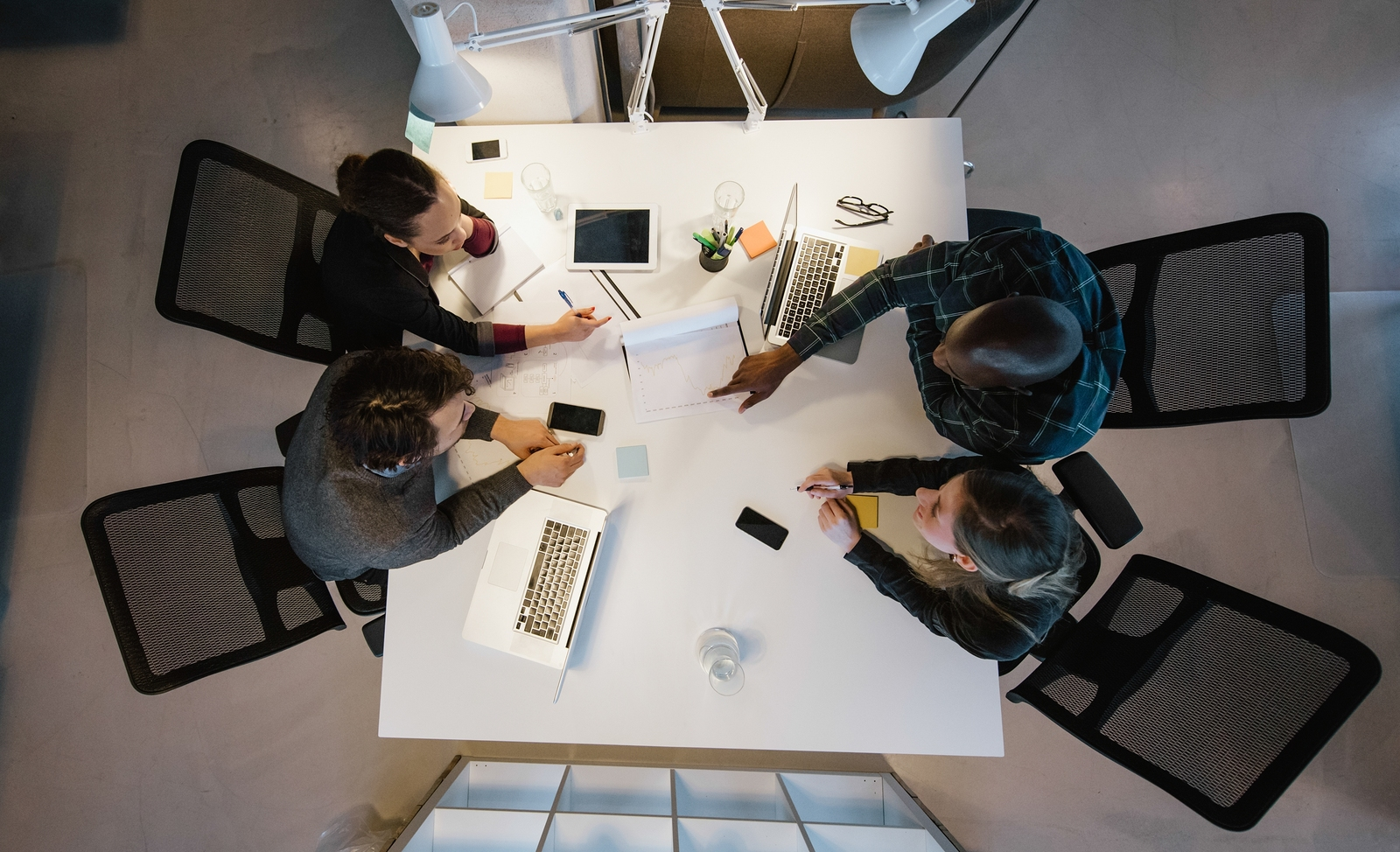 Overhead view of diverse team analyzing data while sitting at office. Multiracial business people in a meeting working on new project.