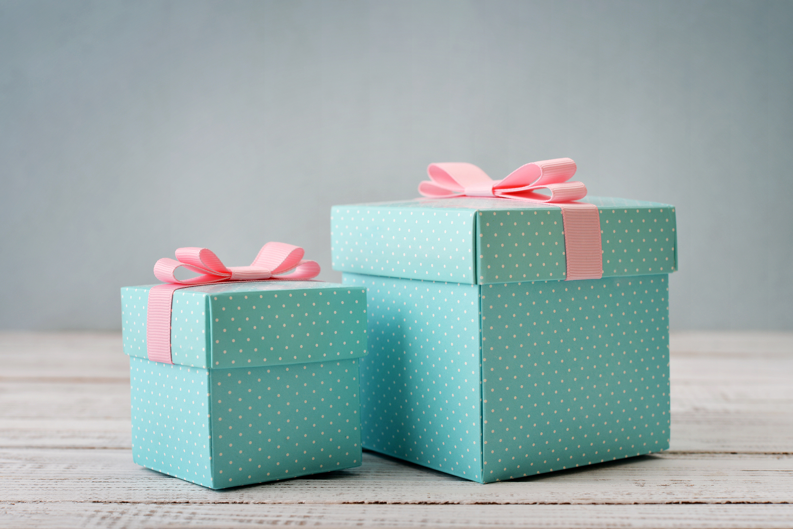 Blue polka dots gift boxes with pink ribbons on wooden background